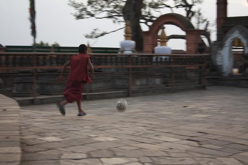 Ein junger Mönch spielt Fußball